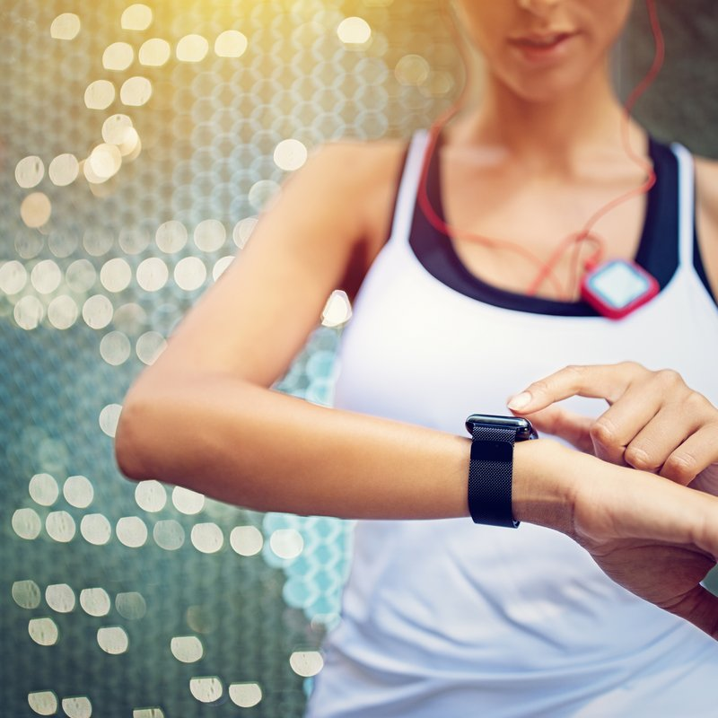 Runner girl is checking her smart watch